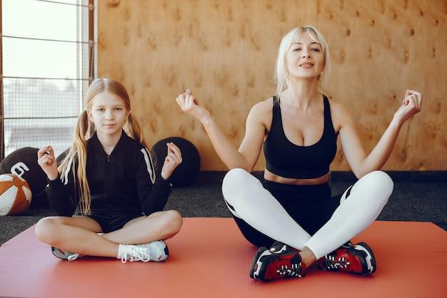 Madre e hija haciendo yoga en un estudio de yoga Foto gratis