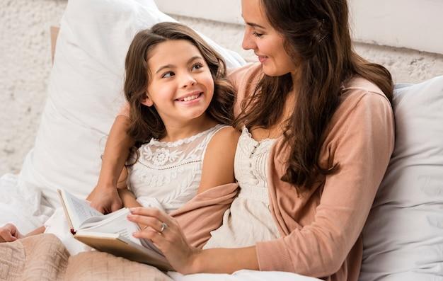 Madre e hija leyendo un libro Foto gratis