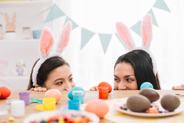 Madre e hija con orejas de conejo mirando por detrás de la mesa con sabrosos huevos de pascua Foto gratis
