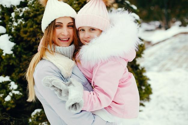 Madre e hija en un parque de invierno Foto gratis