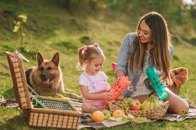 Madre e hija en un picnic con un perro Foto Premium