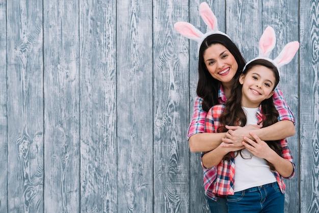 Madre e hija posando delante de fondo gris de madera Foto gratis