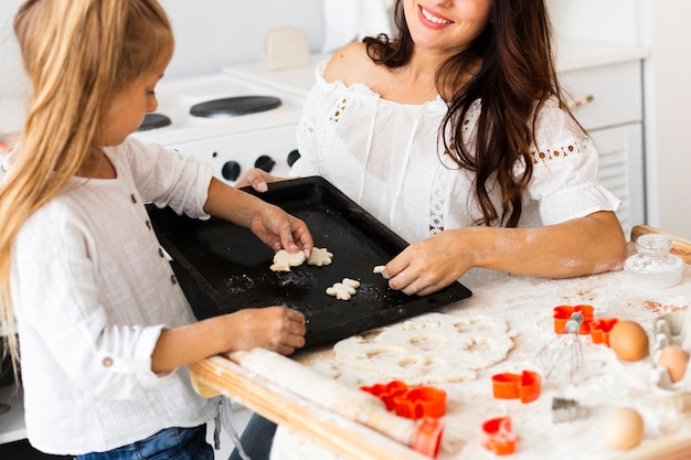 Madre e hija preparándose para hornear galletas Foto gratis