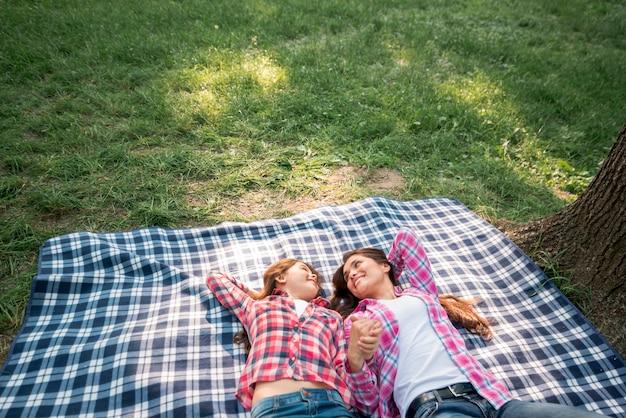 Madre e hija que llevan a cabo su mano que miente en la manta en parque Foto gratis