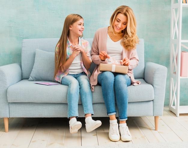 Madre e hija sentadas juntas y abriendo caja actual Foto gratis