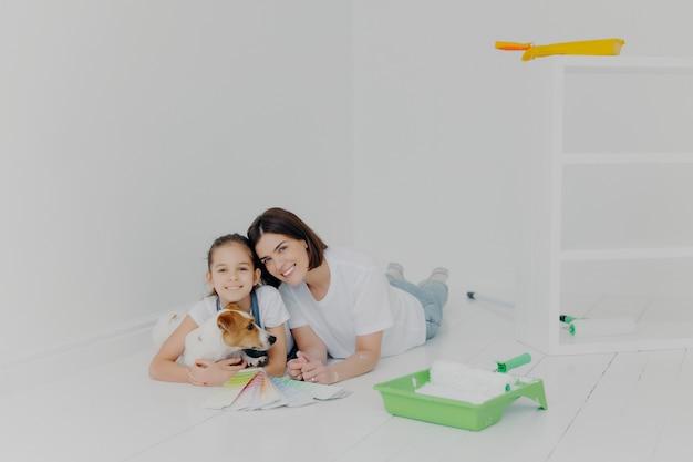 Madre e hija con su perro de pedigrí se encuentran en el piso Foto Premium