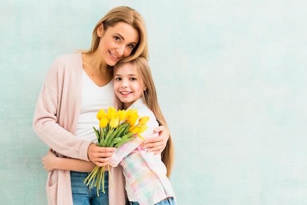 Madre e hija con tulipanes abrazándose y sonriendo Foto gratis