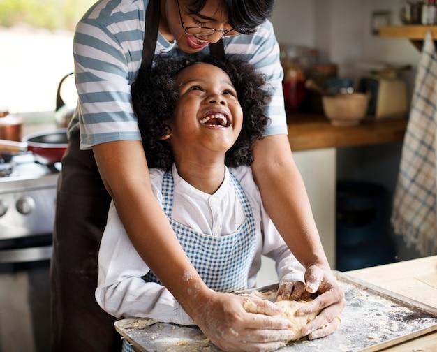 Madre e hijo amasando masa en la cocina. Foto Premium