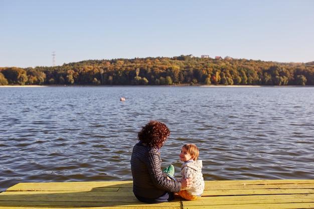 Madre e hijo descansando junto al lago Foto gratis