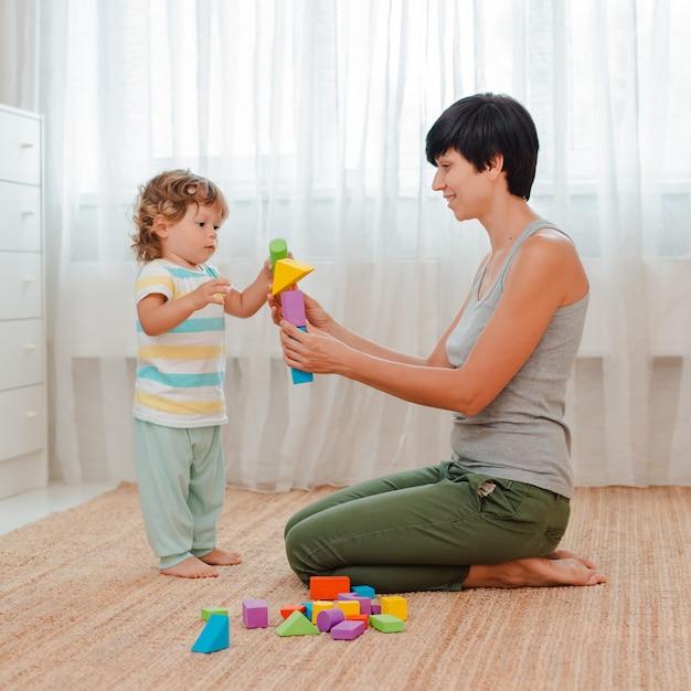 Madre e hijo juegan en el suelo de la guardería. mamá y un niño están construyendo una torre de bloques de colores. Foto Premium