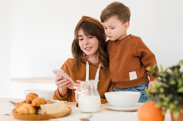 Madre e hijo mirando en el móvil Foto gratis