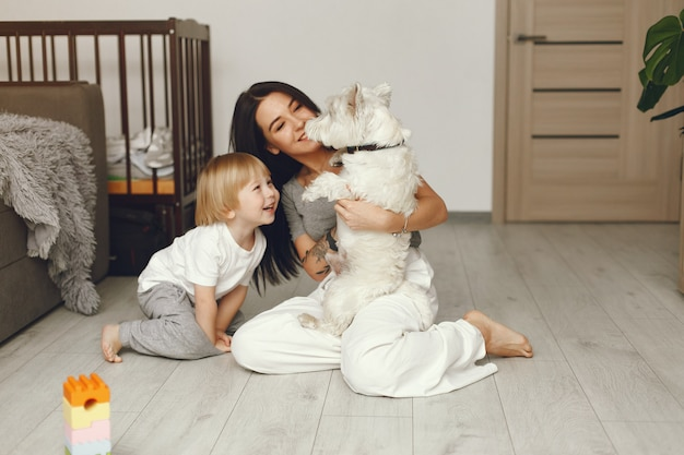 Madre e hijo pequeño divertido en casa con perro Foto gratis