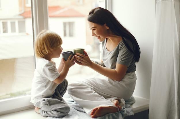 Madre e hijo pequeño sentado en un alféizar con un té Foto gratis