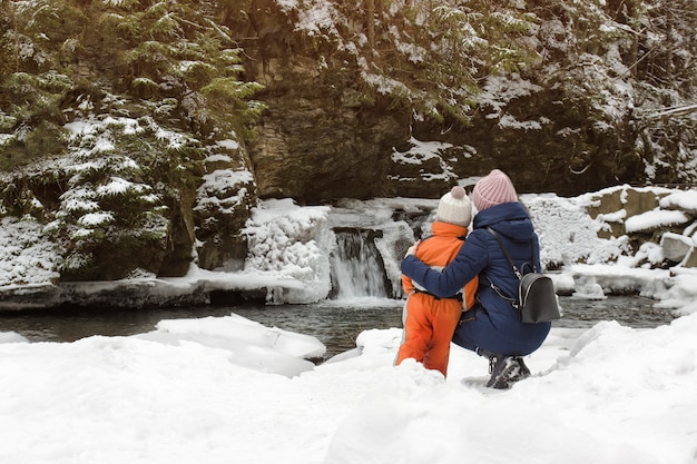 Madre e hijo sentados en un abrazo sobre un fondo de nieve Foto Premium
