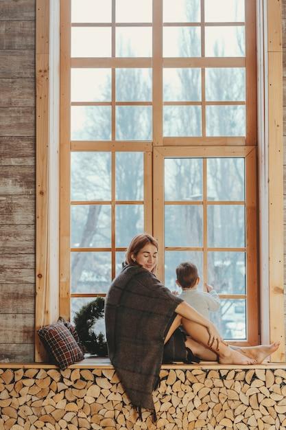 Madre e hijo sentados en el alféizar de la ventana y jugando. Foto gratis