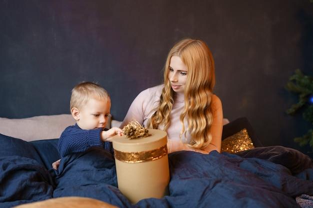 Madre e hijo sentados en la cama abriendo regalos Foto Premium