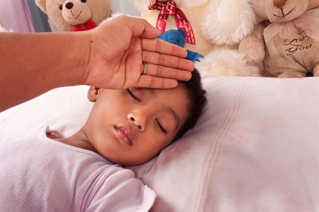 Una madre enferma de un pequeño muchacho asiático cuida Foto Premium