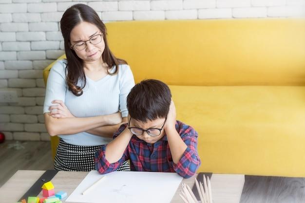 Madre está enojada con su hijo haciendo la tarea Foto Premium