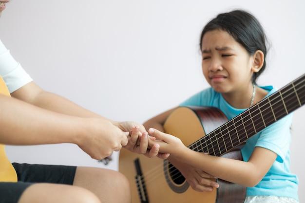 Madre enseñando a la hija a aprender a tocar la guitarra acústica clásica Foto Premium
