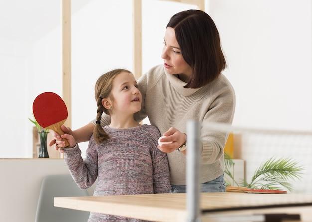 Madre enseñando hija ping pong Foto gratis