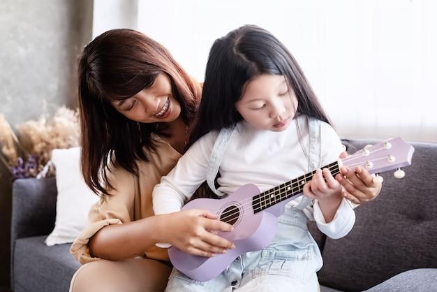 Madre enseñando a su hija a tocar el ukukele, hacer actividades juntos, relajarse, en la sala de estar, luz borrosa alrededor Foto Premium