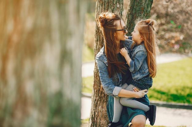 Madre con estilo con el pelo largo y una chaqueta de jeans jugando con su pequeña hija linda Foto gratis