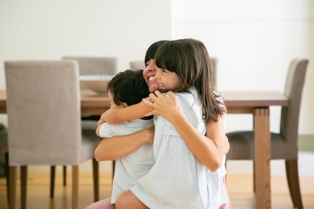 Madre feliz abrazando a sus adorables hijos con ambas manos. Foto gratis