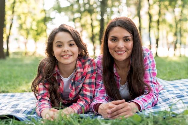 Madre feliz e hija que miran la cámara que miente en la manta sobre tierra herbosa en parque Foto gratis