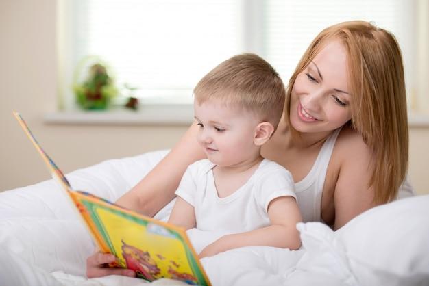 Madre feliz con el libro de lectura del bebé junto. Foto Premium