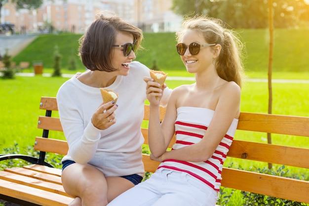 Madre feliz y linda hija adolescente en el parque de la ciudad Foto Premium