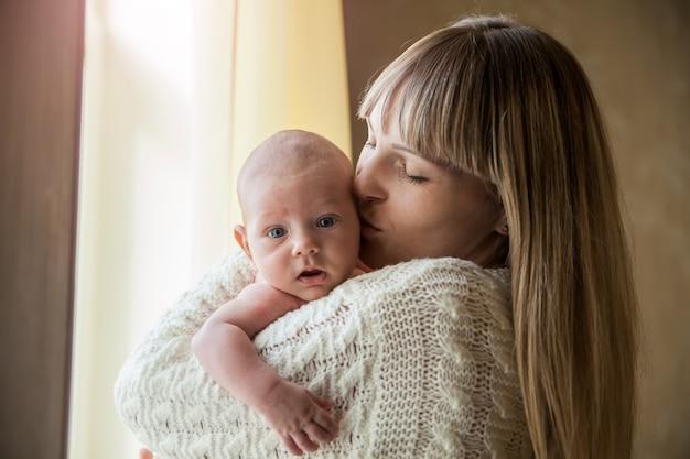 Madre feliz que celebra a su bebé en casa por la ventana Foto Premium