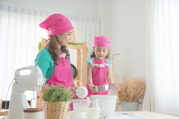 Madre hermosa e hija asiáticas que llevan el delantal rosado que hace la torta en la cocina. Foto Premium