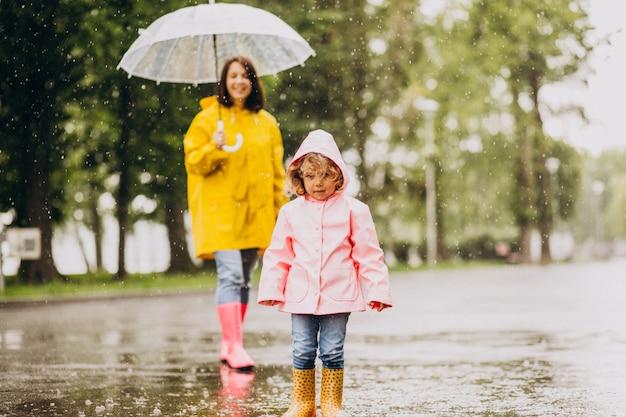 Madre con hija caminando bajo la lluvia bajo el paraguas Foto gratis