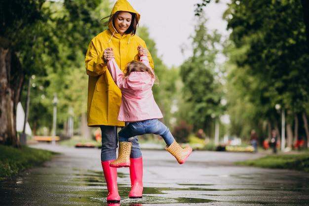 Madre con hija divirtiéndose en el parque en un clima lluvioso Foto gratis