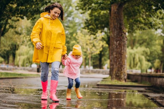 Madre con hija divirtiéndose saltando en los charcos Foto gratis
