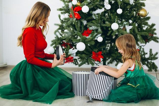 Madre con hija empacando regalos por arbol de navidad Foto gratis