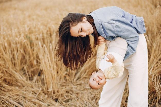 Madre con hija jugando en un campo de otoño Foto gratis