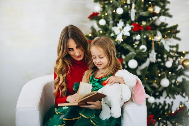 Madre con hija leyendo libro por arbol de navidad Foto gratis