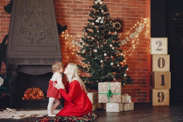 Madre con hija linda en casa en un vestido rojo Foto gratis