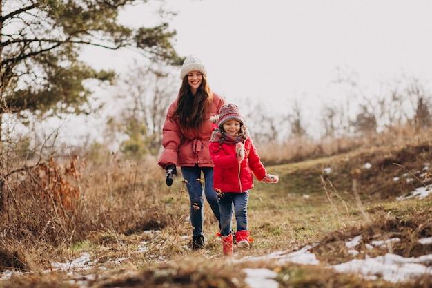 Madre con hija pequeña en un bosque de invierno Foto gratis