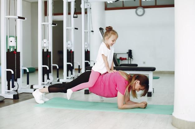 Madre con hija pequeña se dedican a la gimnasia en el gimnasio. Foto gratis