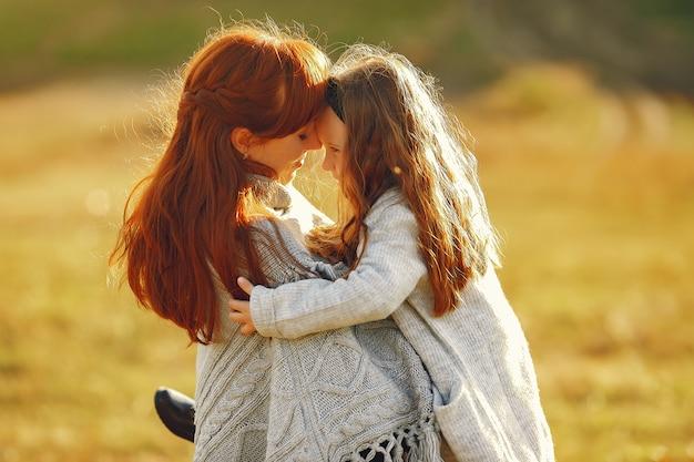Madre con hija pequeña jugando en un campo de otoño Foto gratis
