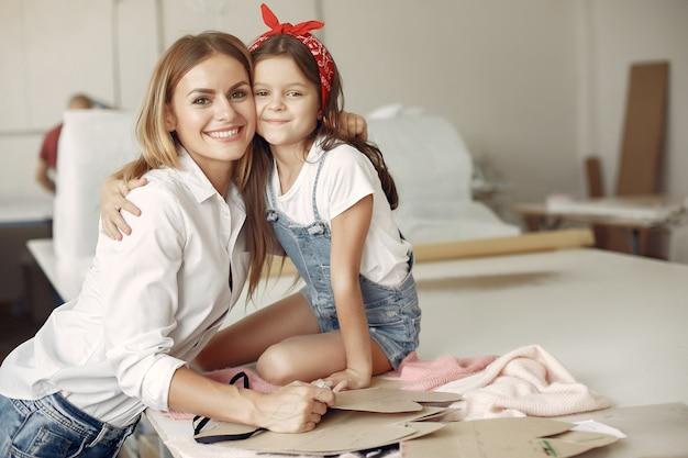 Madre con hija pequeña medir la tela para coser Foto gratis