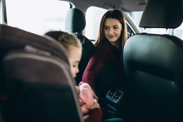 Madre con hija pequeña sentada en la parte trasera del automóvil en un asiento de seguridad Foto gratis