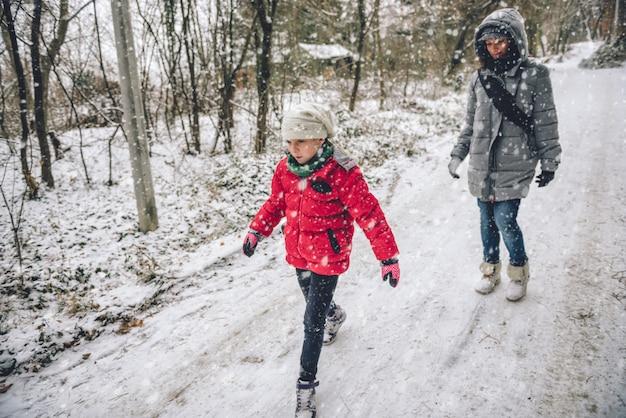 Madre con hija senderismo en bosque nevado Foto Premium