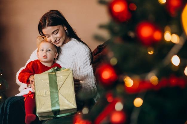 Madre con hija sentada junto al árbol de navidad Foto gratis