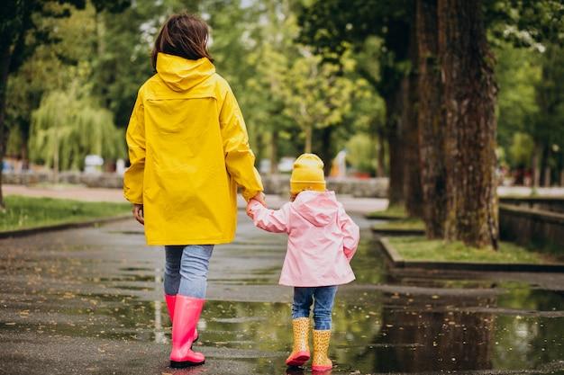 Madre con hija vistiendo abrigo y botas de goma caminando en un clima lluvioso Foto gratis