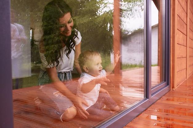 La madre y el hijo mirando la ventana Foto gratis