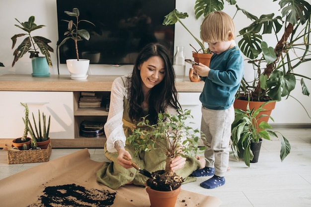 Madre con hijo pequeño cultivando plantas en casa Foto gratis