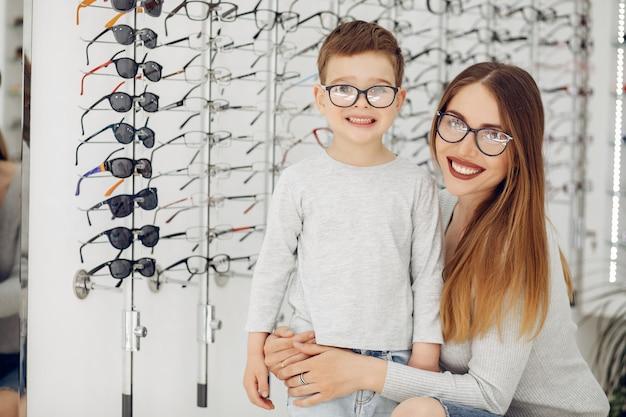 Madre con hijo pequeño en la tienda de gafas Foto gratis